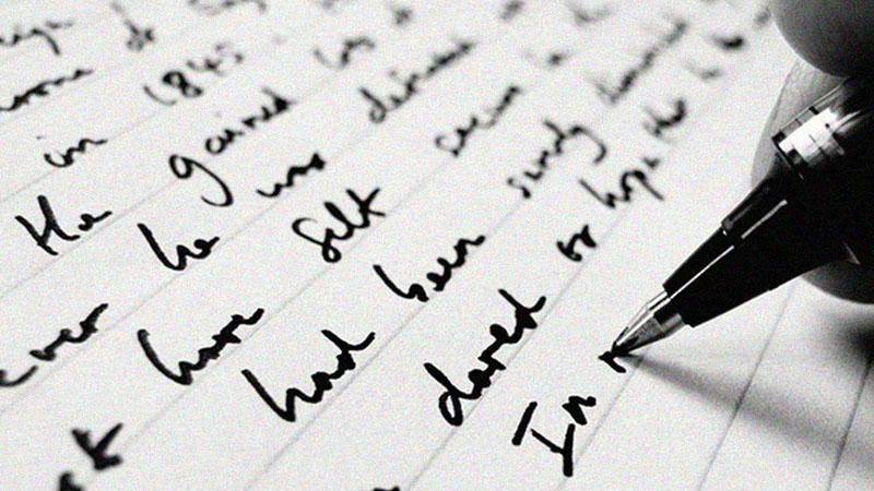 Black pen writing cursive on lined paper